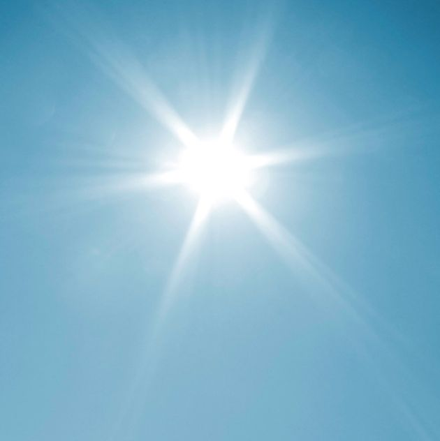 Sun with bright rays against a blue sky
