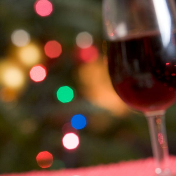 Glass of red wine with holiday lights in background
