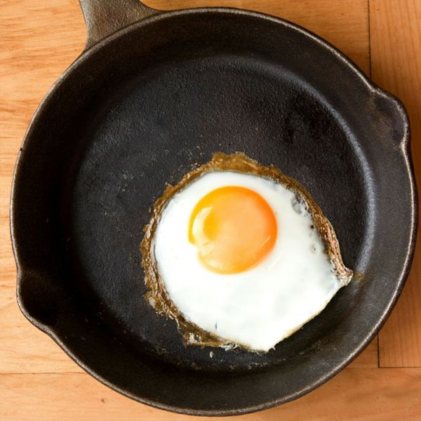 Fried Egg with crispy edges in an iron skillet on a wood countertop