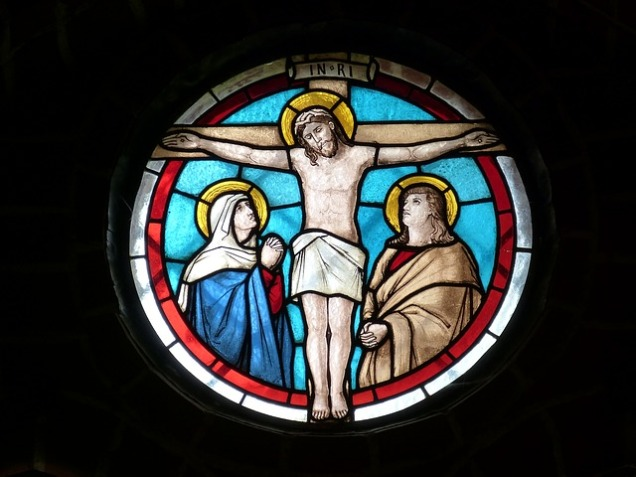 Stained glass window of Jesus Christ on crucifix flanked by Virgin Mary and Saint John the Evangelist