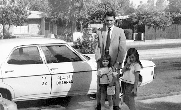 My father, sister & I are standing in front of a taxi cab in the Dhahran ARAMCO compound where we lived. I was 7. My sister 4. We are wearing matching sailor dresses as we are about to embark on an adventure as we travel and return to the States.