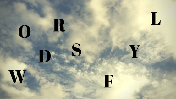 Words Fly - WORDS is jumbled. FLY is jumbled and on a diagonal rise. Background is wispy clouds.