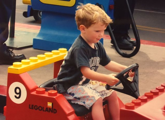 My son as a toddler carefully driving a small Lego car at Legoland