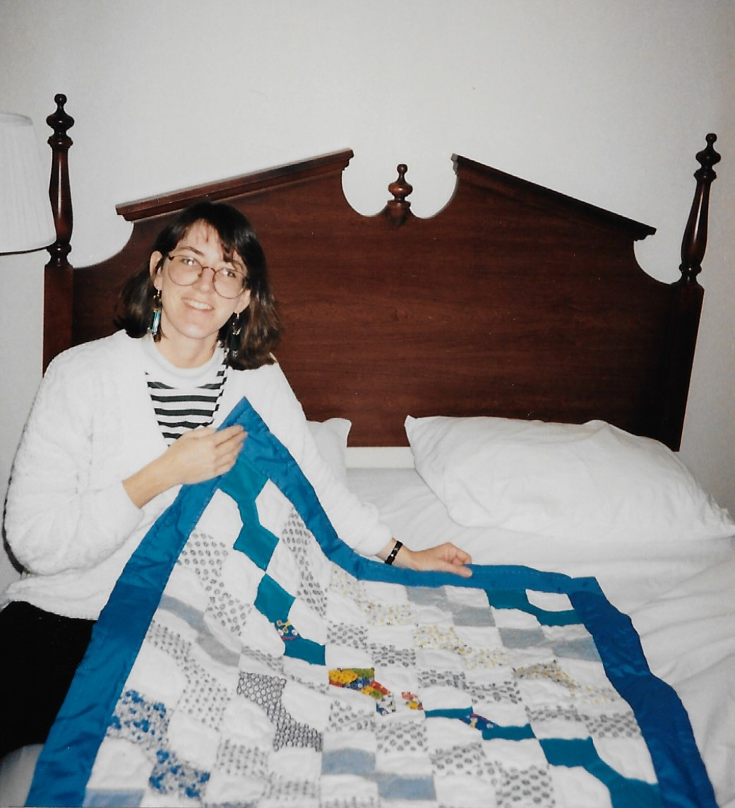 Sitting on bed holding up end of small bow tie quilt
